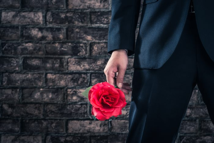 バラの花を持っているスーツの男性