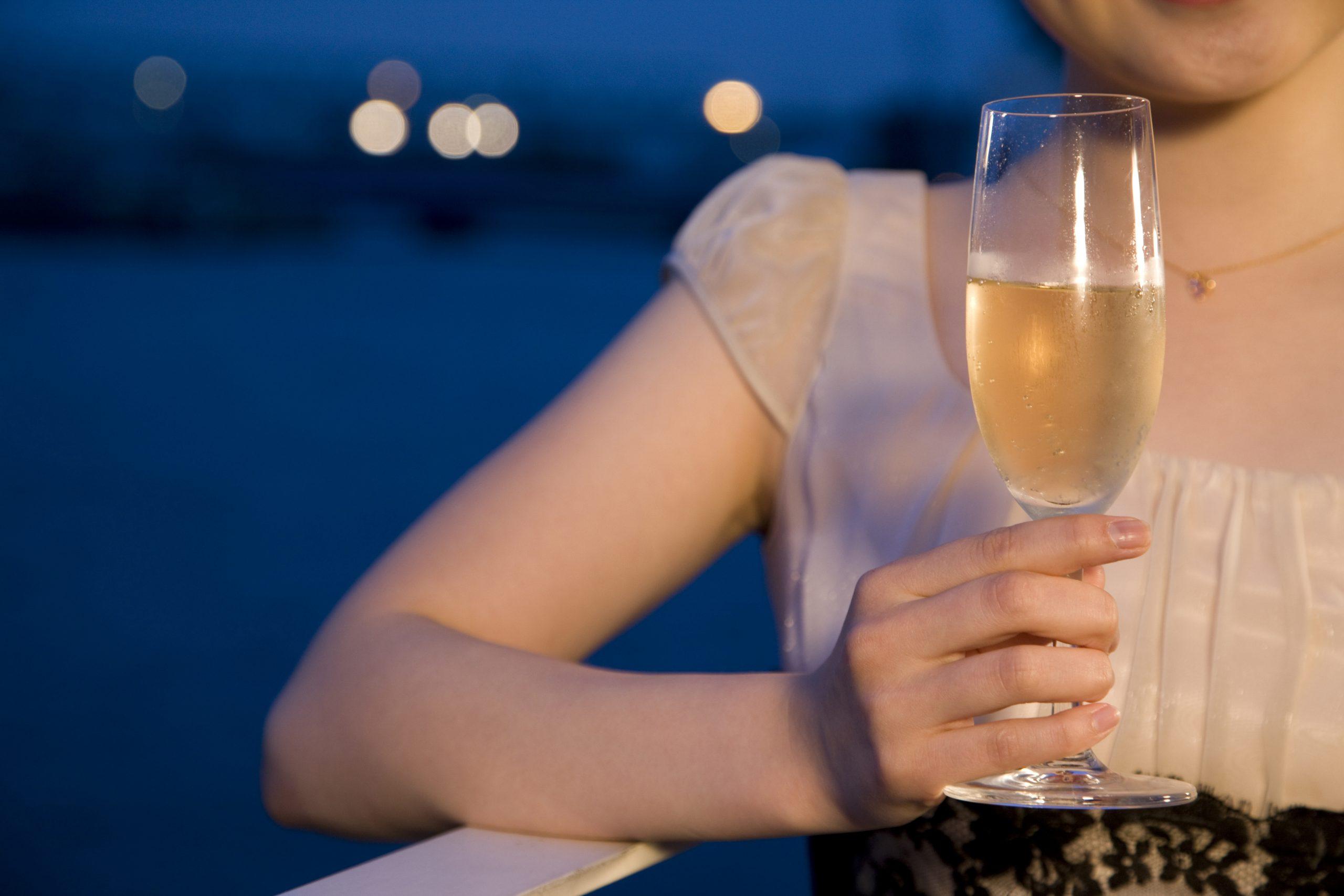 テラスでシャンパンを飲む女性の手元