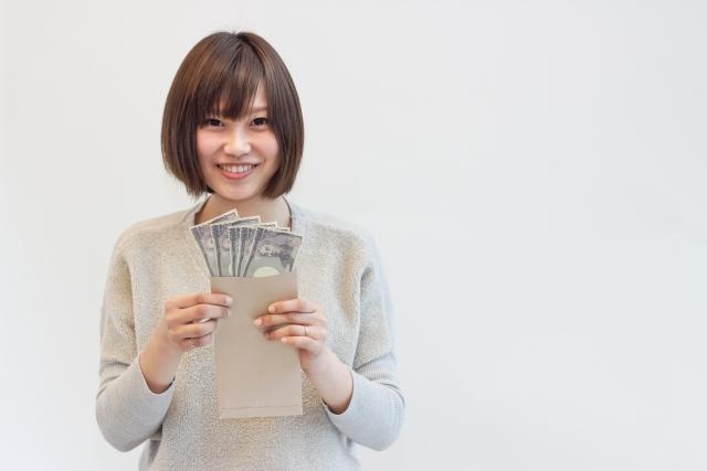 お金を持つ笑顔の女性