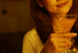 カクテルグラスを片手に持つ女性