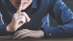 口元に指を当てシーというポーズをする男性。秘密のジェスチャー