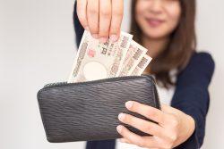 お札を財布から出す女性