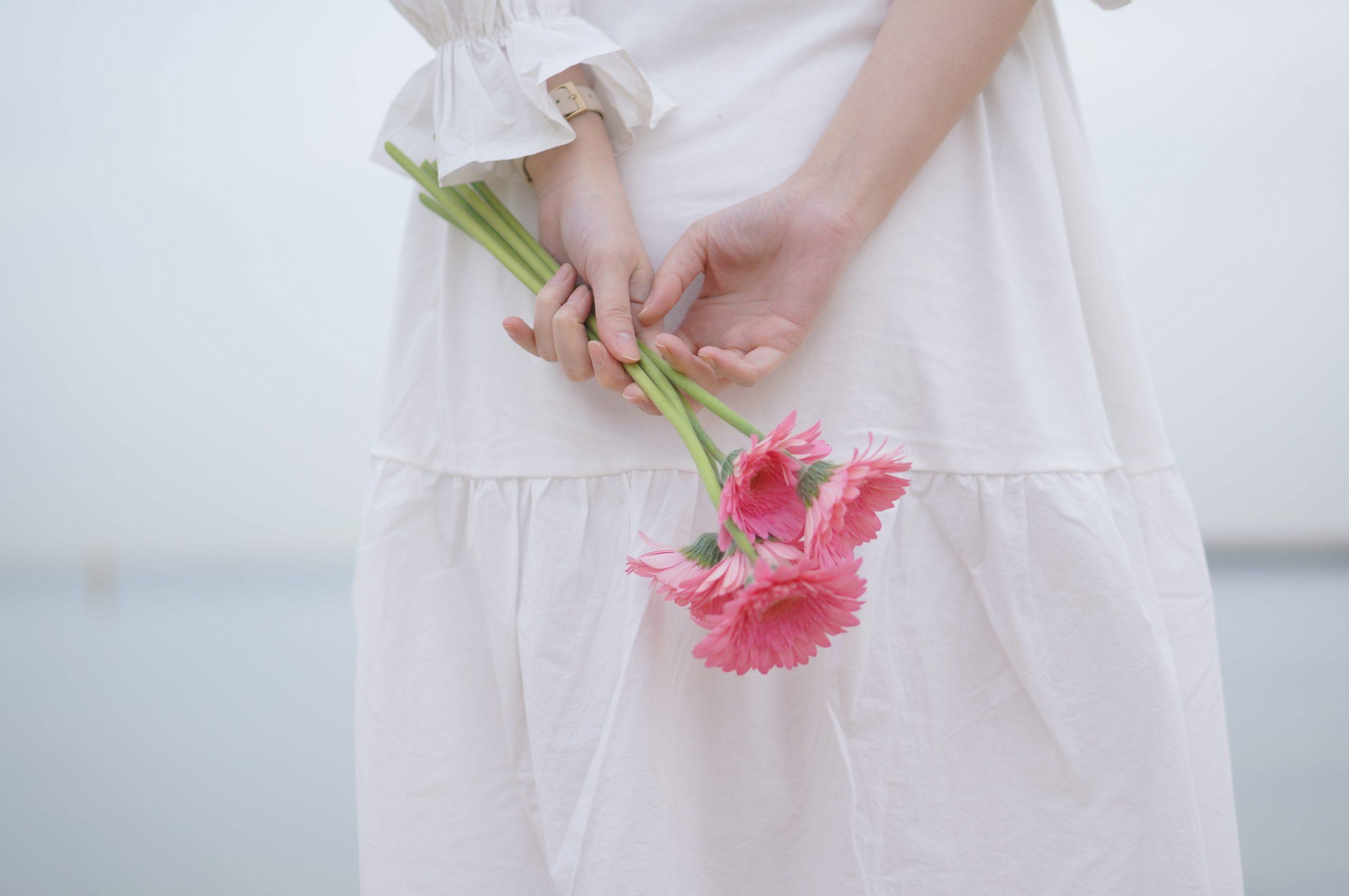 背中でお花を持つ女性