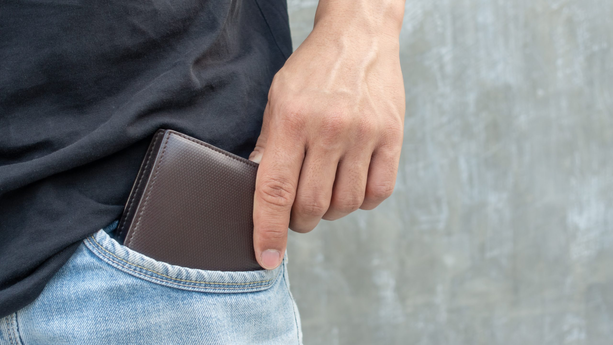 Men hold a brown wallet from a jeans pocket.