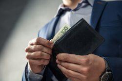 男性がお金を財布から出すシーン