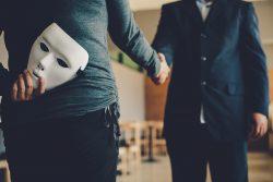 男性と握手する詐欺師