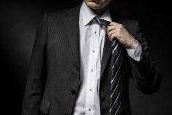 ネクタイを緩めるスーツ姿の男性