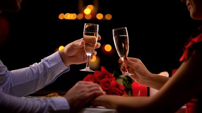 Couple holding glasses with champagne, male stroking lady hand tenderly, romance
