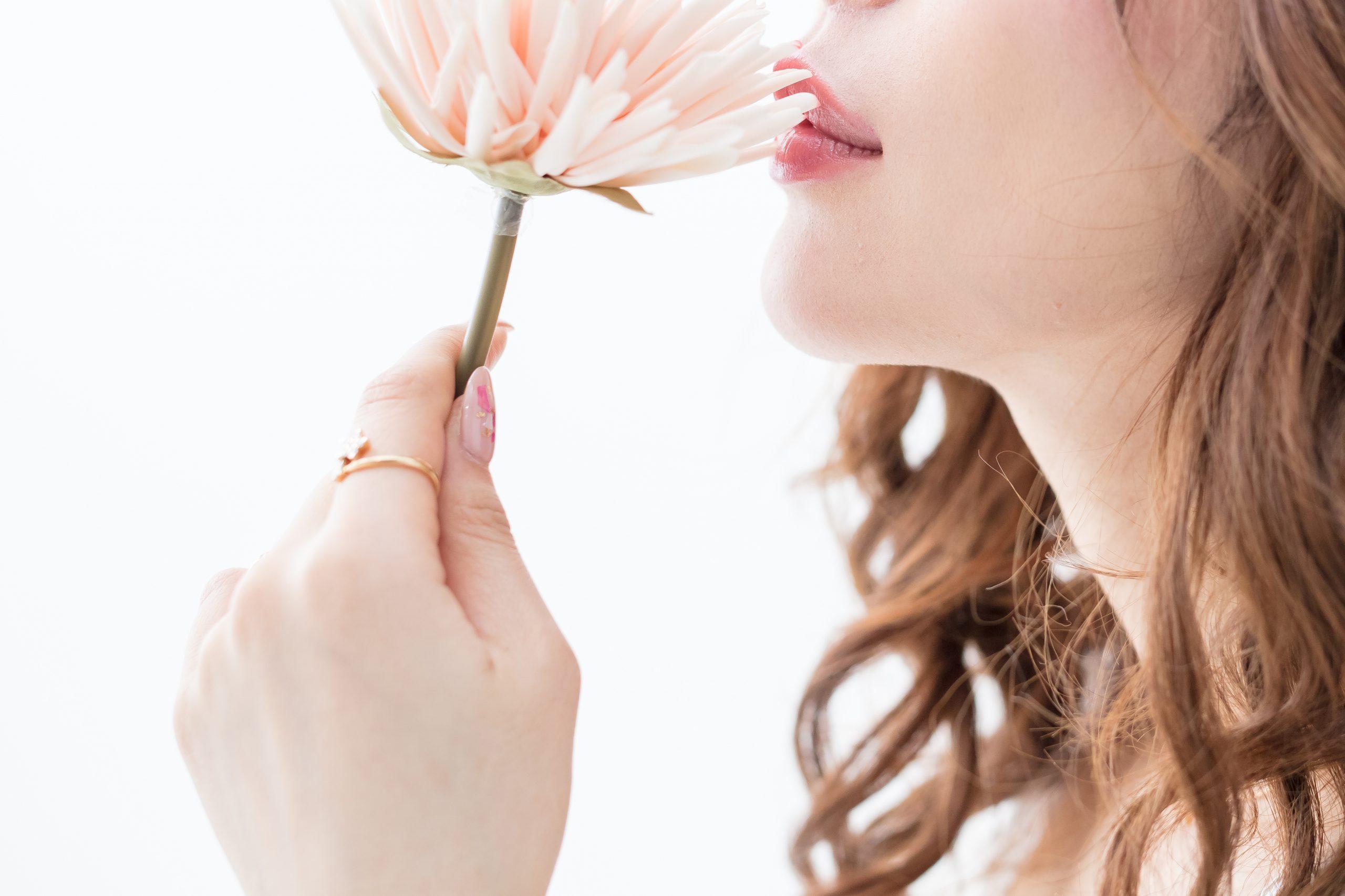 白背景に茶髪の巻き髪をした綺麗な女性が花をもって上を向いている