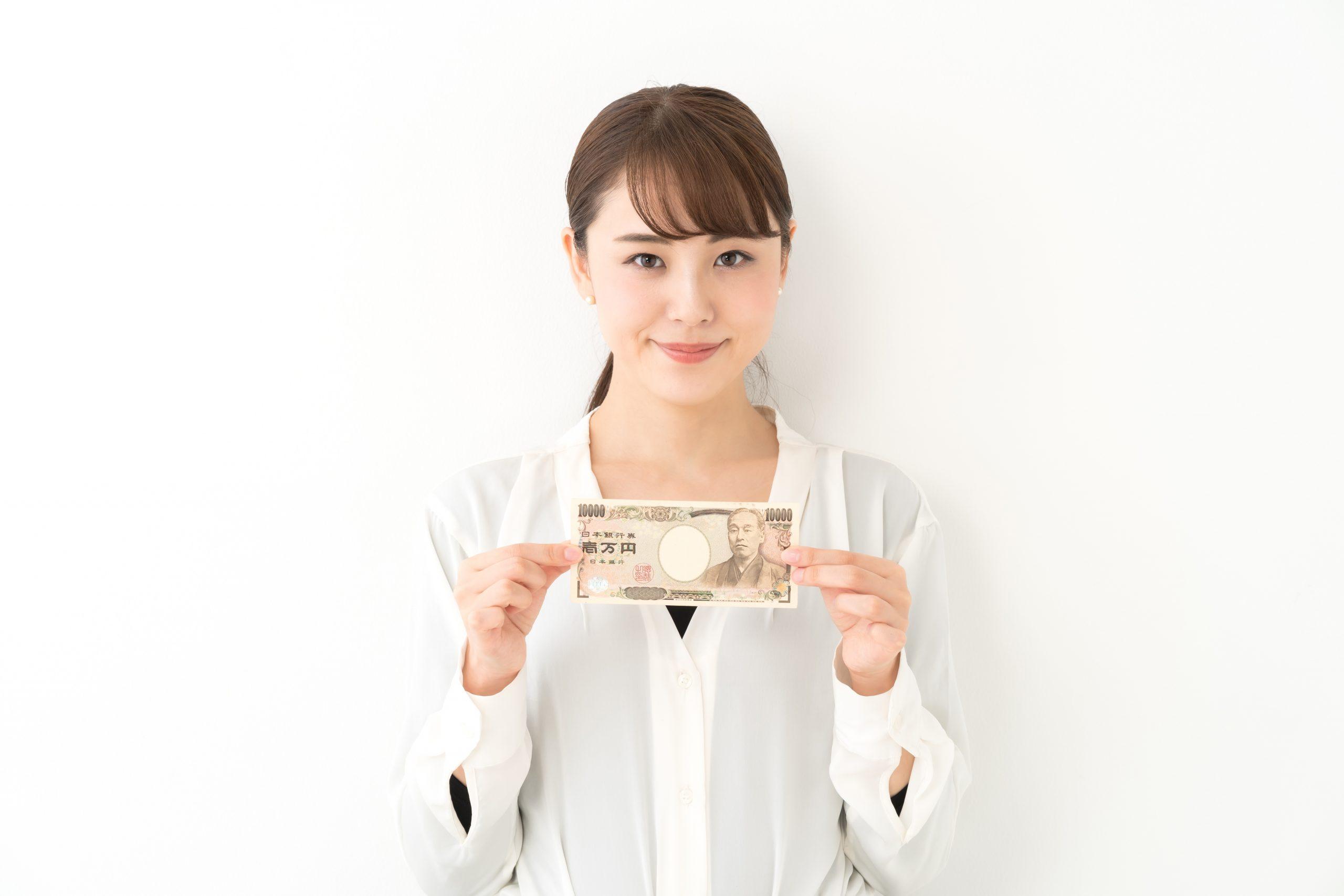 お金を両手で持つ笑顔の女性