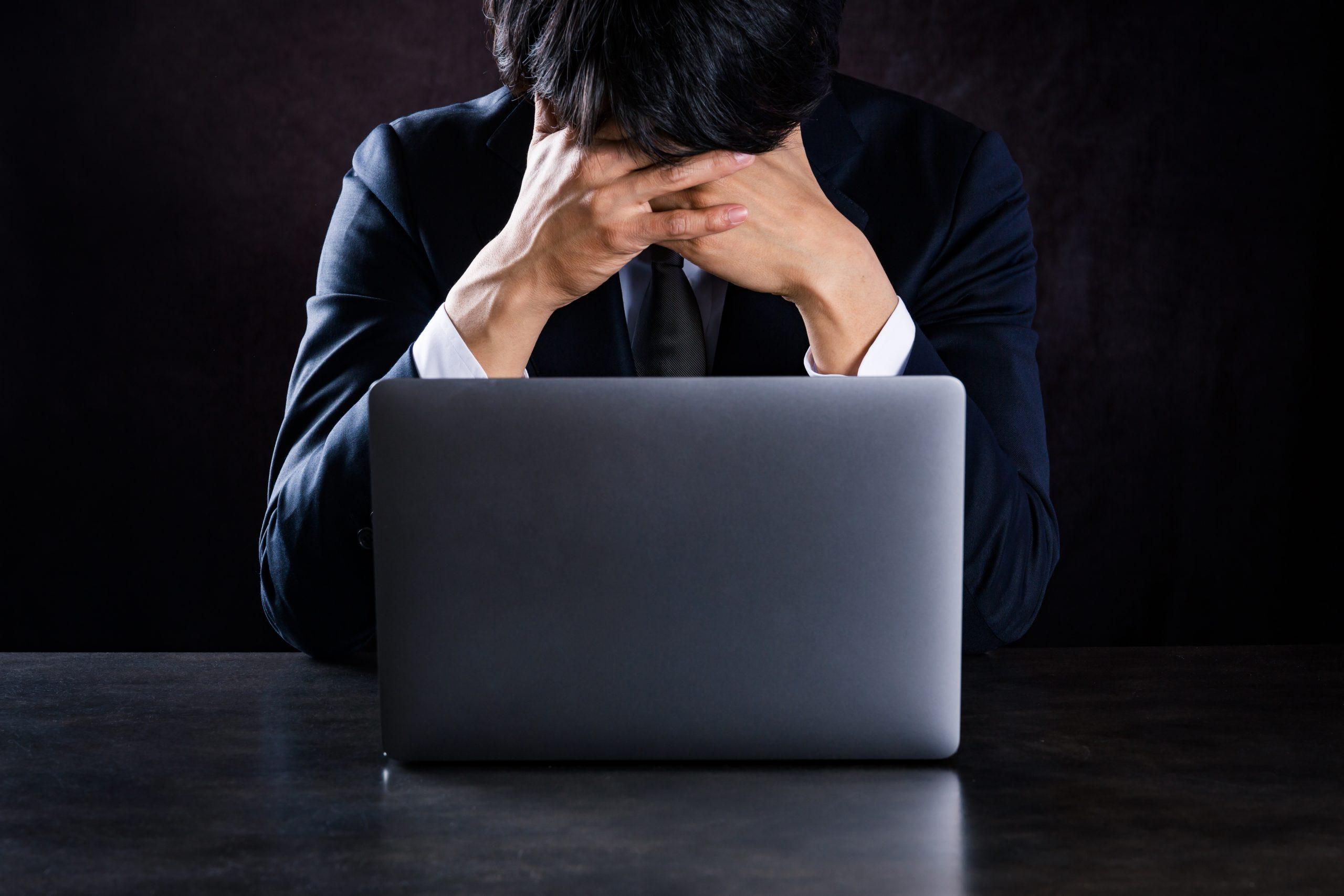 ノートパソコンの前で疲労した男性
