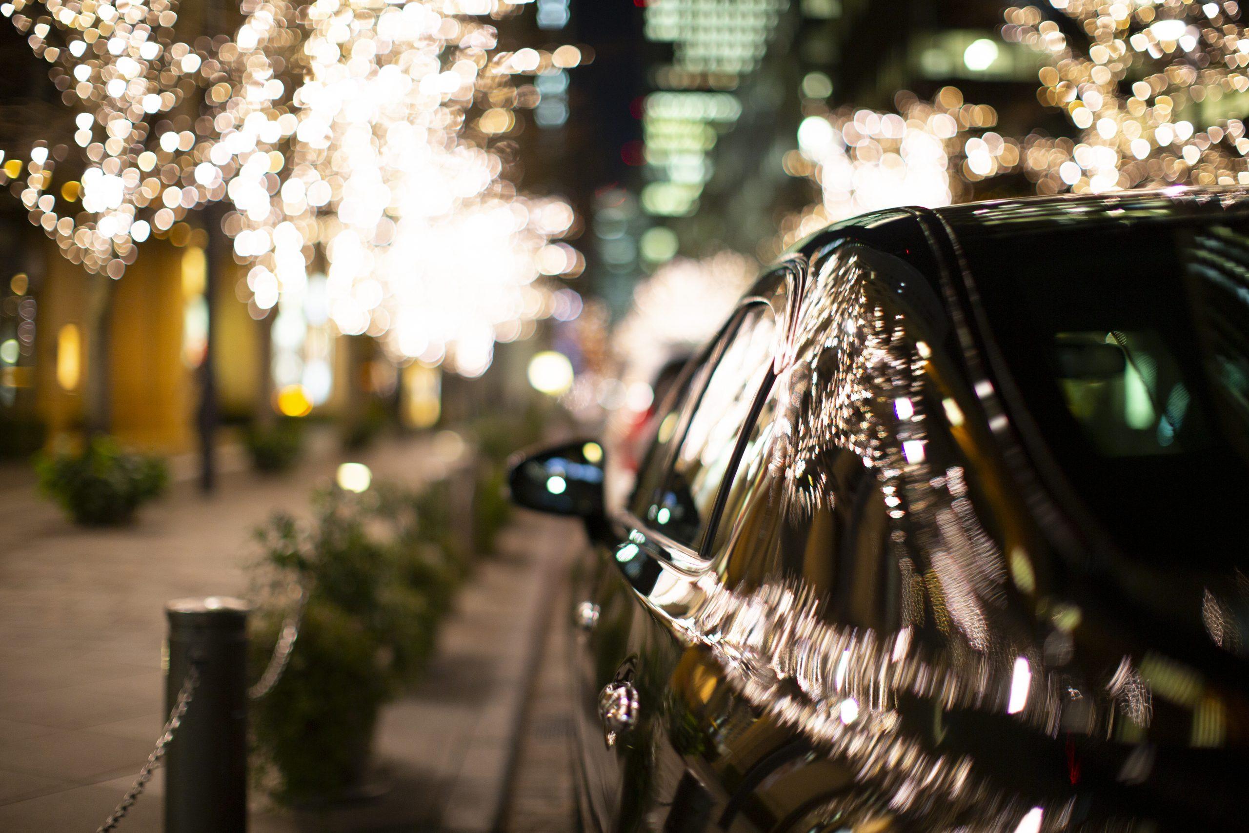 クリスマスのイルミネーションを反射する高級車