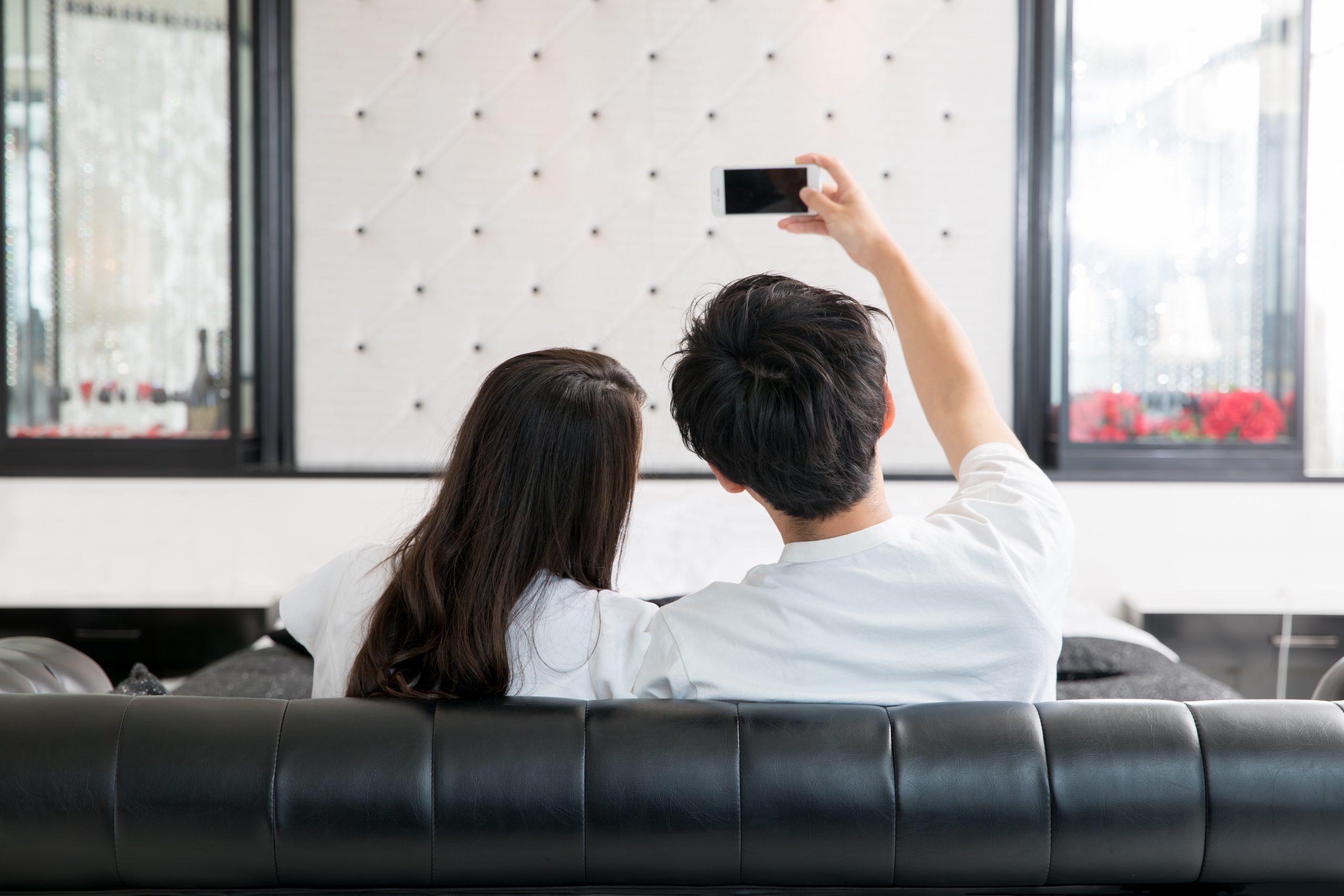 ソファで自撮りするカップル