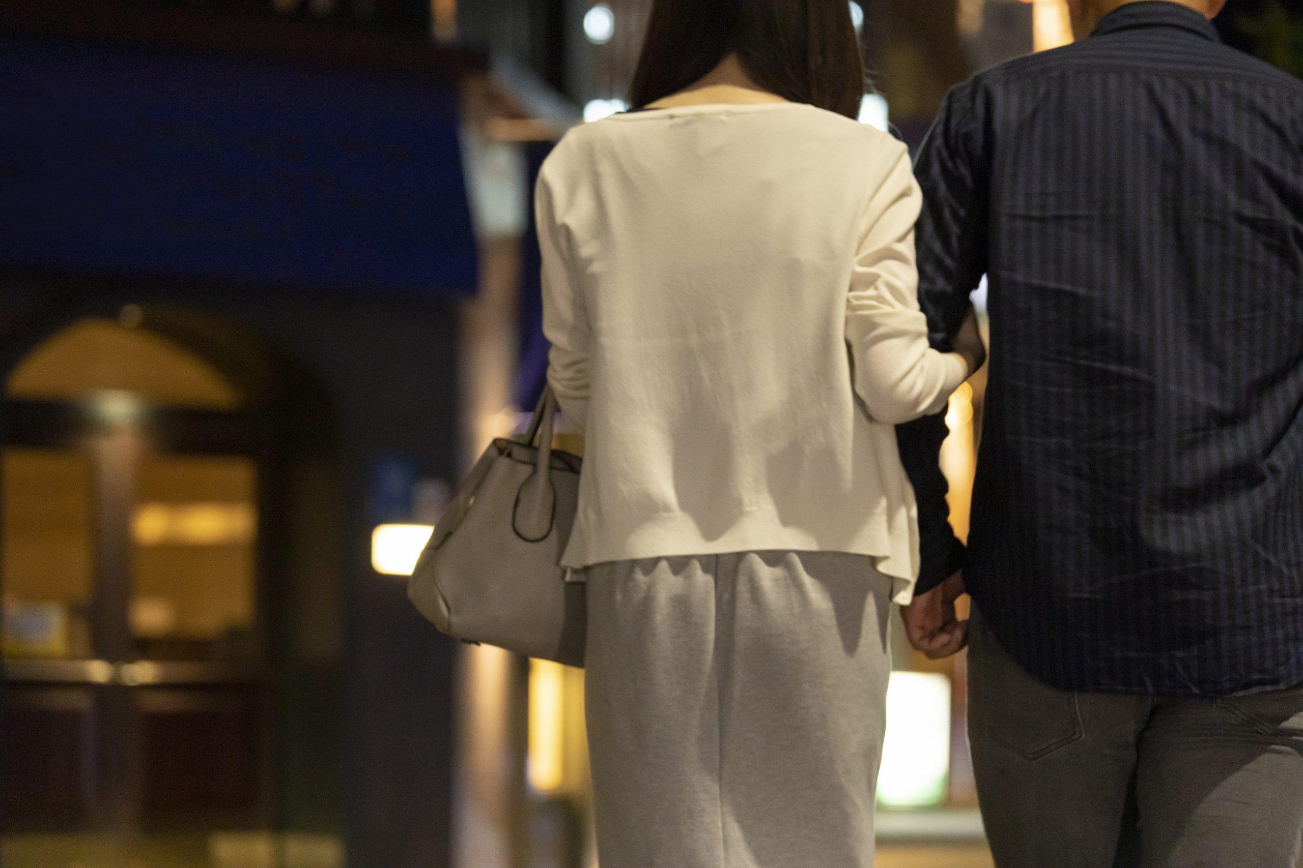 夜の繁華街で手を繋いで歩く男女の後ろ姿