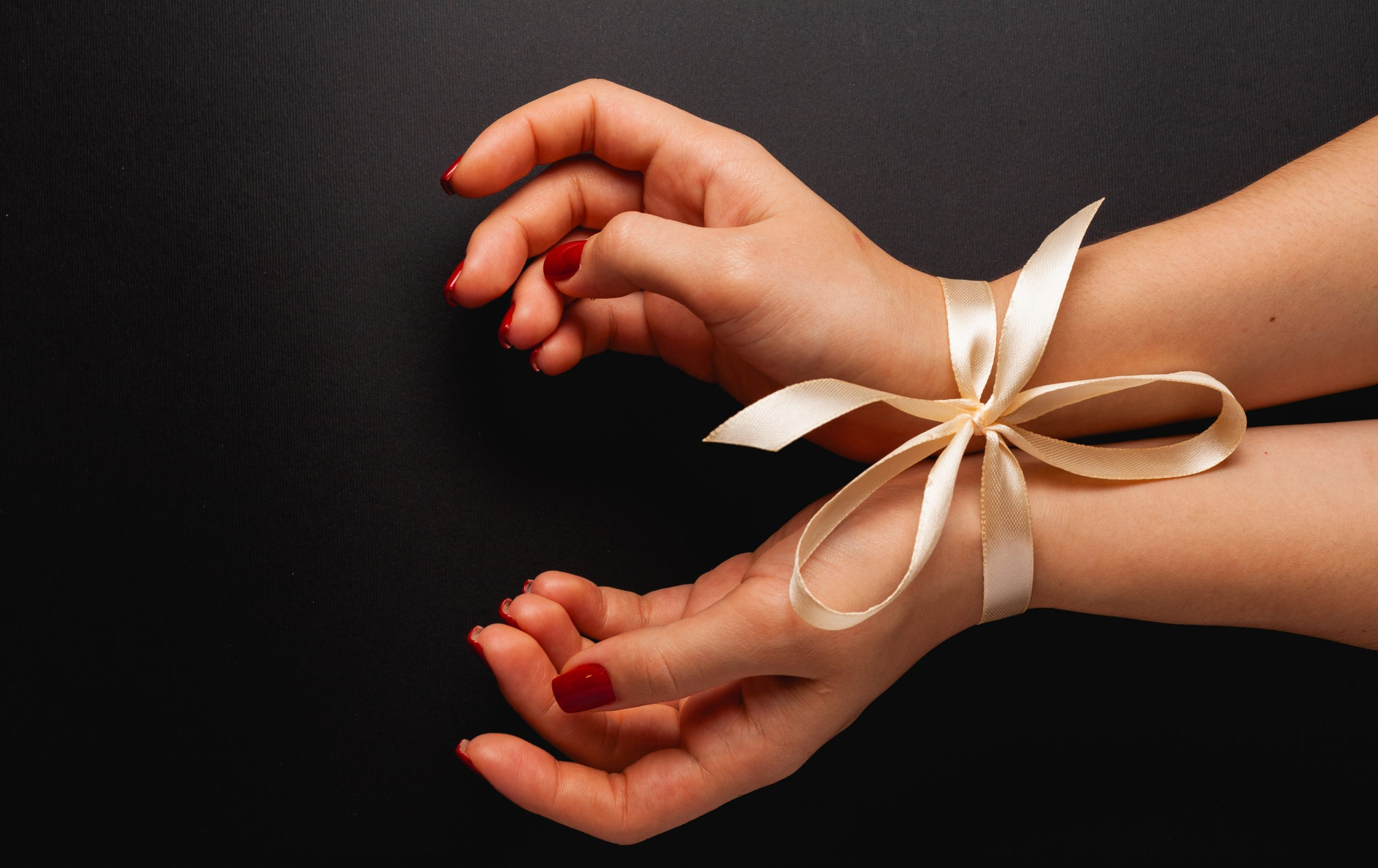 Beautiful female hands tied on a black background. Top view with place for text.