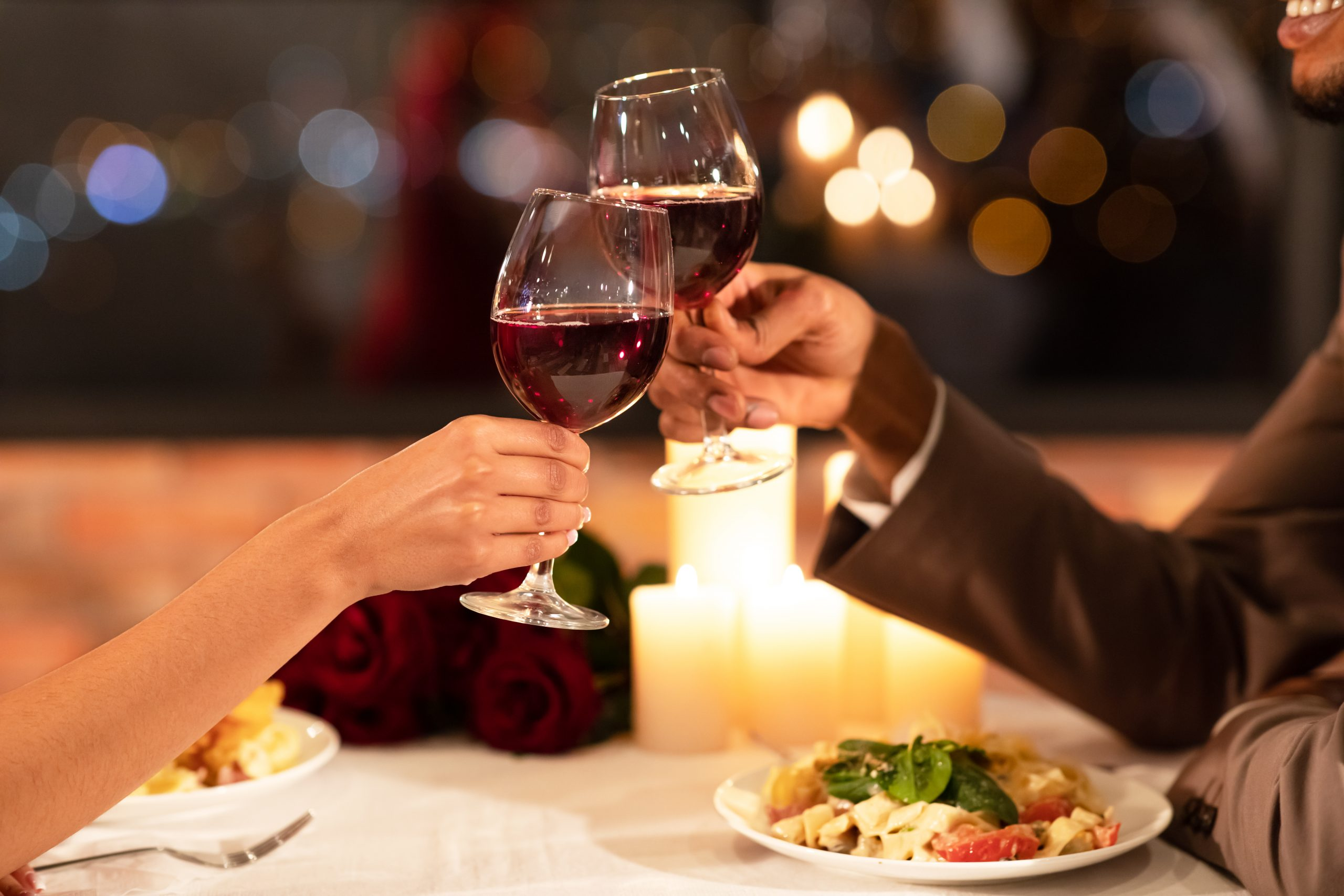 Couple's Hands Clinking Glasses Of Red Wine Dating In Restaurant