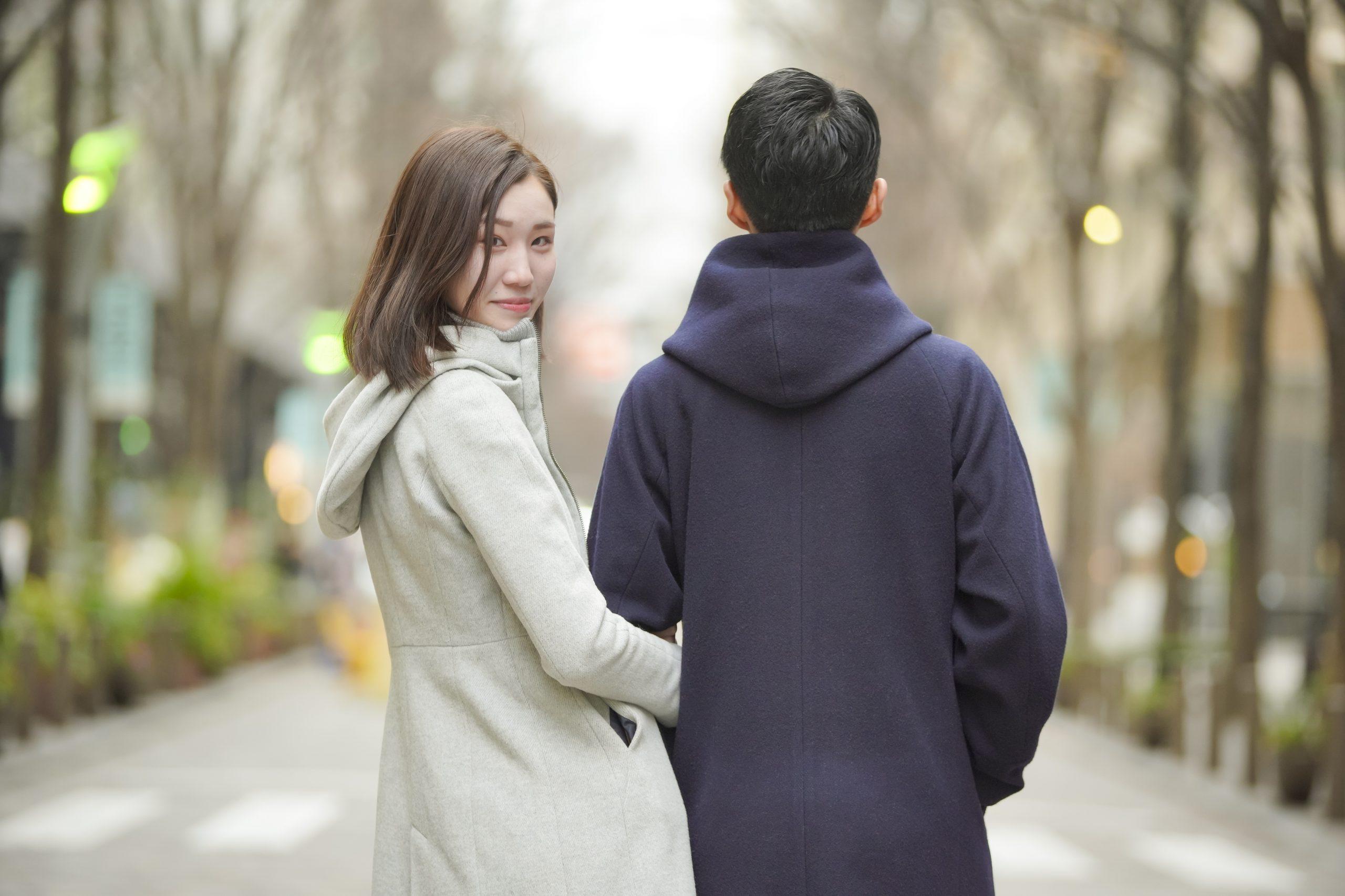 街を歩くカップルと振り返る女性