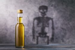 A bottle of whiskey with a shadow in the shape of a skeleton. Concept on the harm of alcohol and harmful habits of man