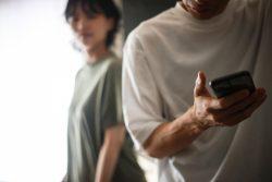 スマートフォンを操作する男性と怪しげにみる女性