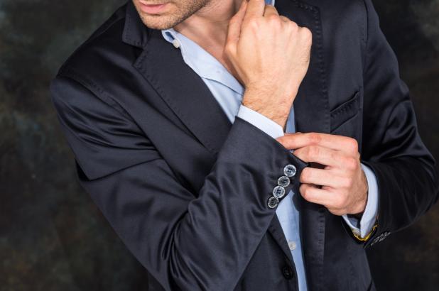 スーツの腕ボタンを外す色気のある男性
