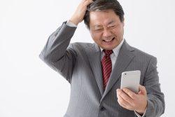 携帯電話を持つビジ頭をかく中年男性