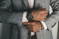 Businessman luxury style. Men style.closeup fashion image of luxury watch on wrist of man.body detail of a business man.Man's hand in a grey shirt with cufflinks in a pants pocket closeup. Toned