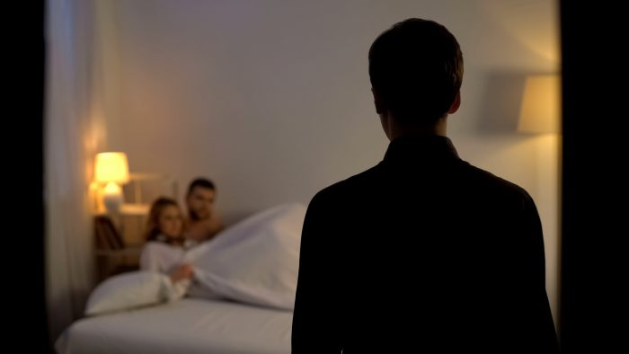 Man looking at his wife with lover in bed, unfair relations, partner cheating