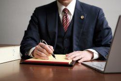 リーガルパッドにメモをする男性弁護士