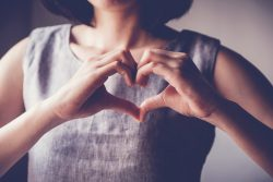 young woman making her hands in heart shape, heart health insurance, social responsibility, donation charity, world heart day, appreciation, world mental health day concept