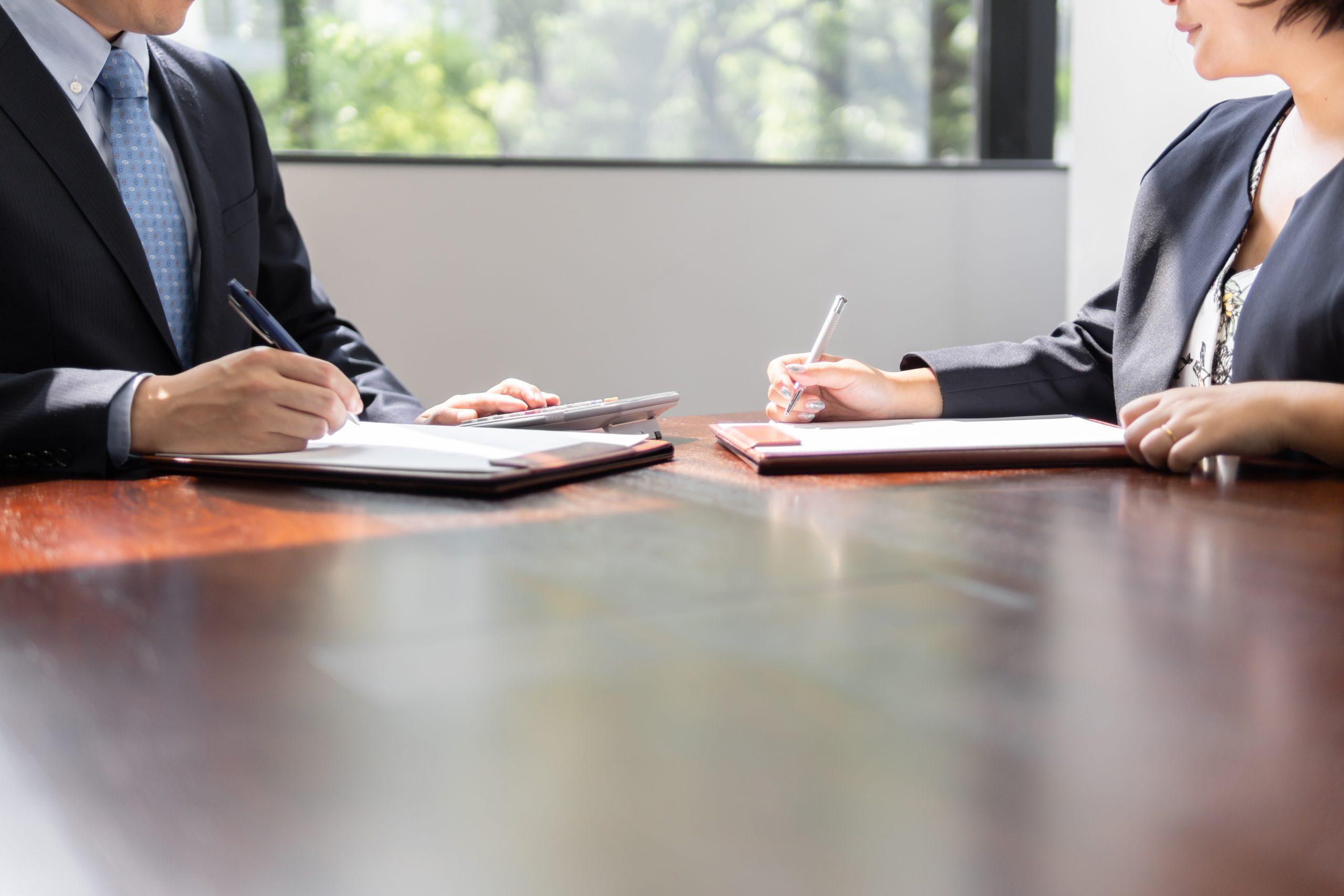 明るい会議室で打ち合わせをするビジネスマンとビジネスウーマン