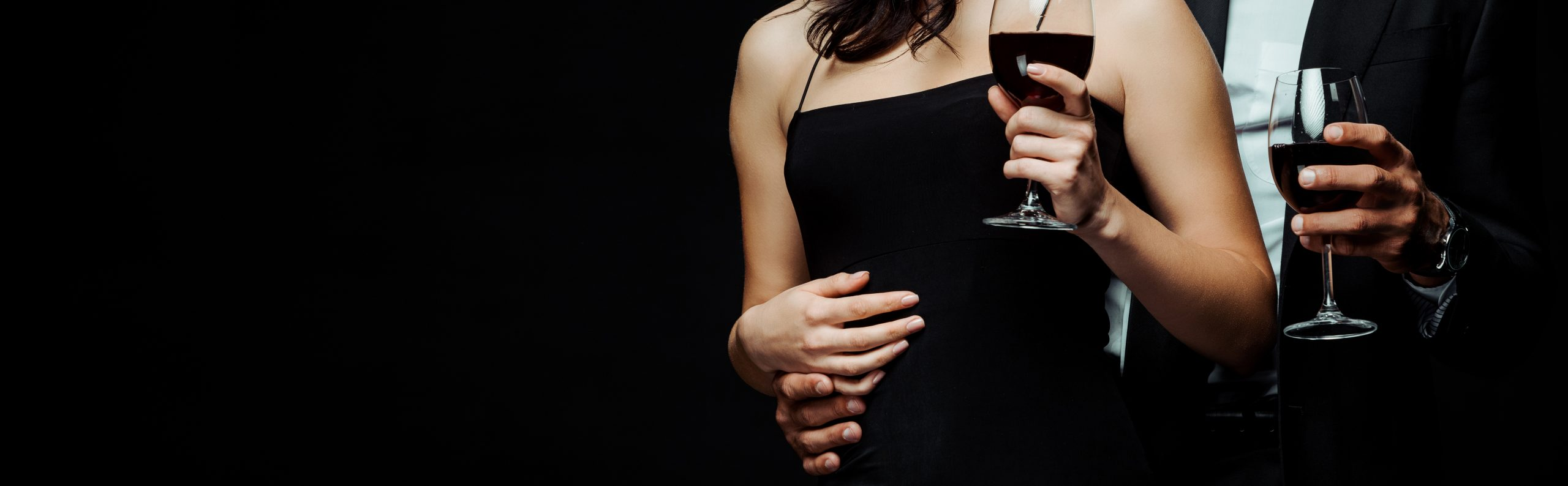 panoramic shot of couple holding glasses with red wine isolated on black