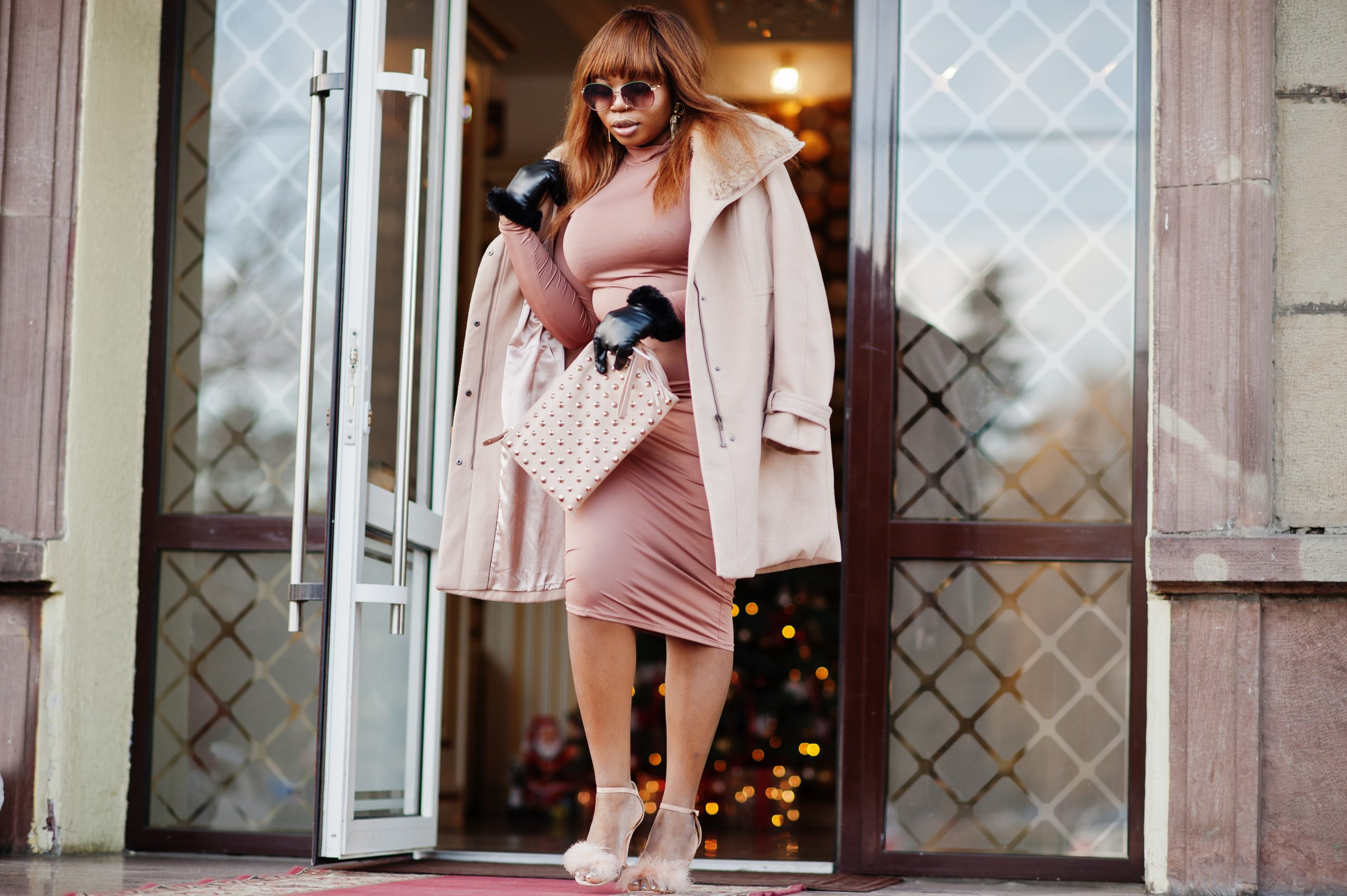 Maxi plus size rich african american model woman in dusty rose silk dress with coat and gloves, sunglasses posed outdoor near door of hotel.