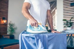 Dark-haired young man in white tshirt ironing his shirt