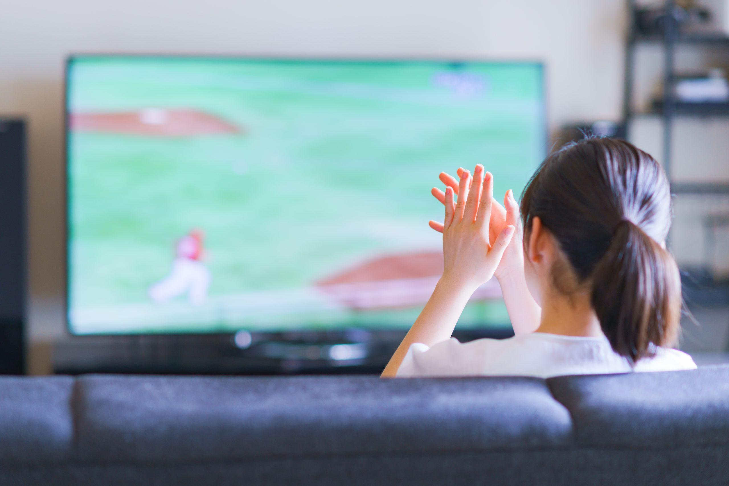 家でスポーツをテレビ観戦する若い女性