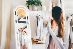 Pretty brunette woman in pink skirt talks on mobile phone choosing elegant clothes in wardrobe room in light contemporary apartment at home