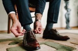 The groom morning before wedding ceremony wears shoes. Businessman tie the laces on the shoes. Men's style. Professions. To prepare for work, to the meeting.
