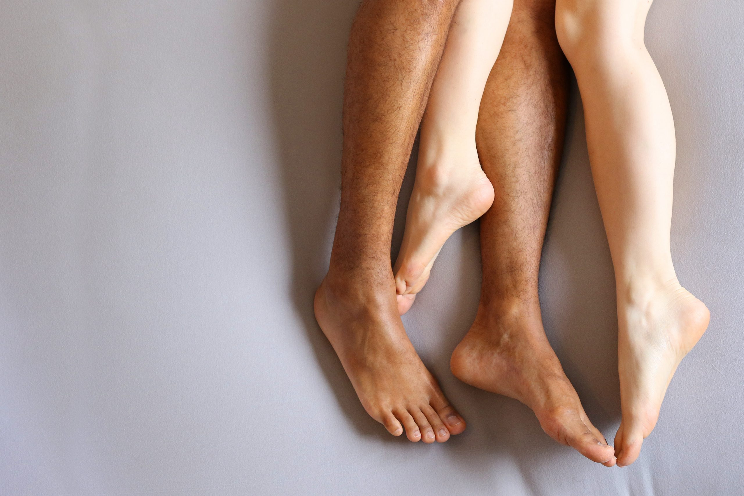 Legs of interracial couple in bed - copy space