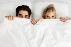 Young loving couple lying on the bed, peaking