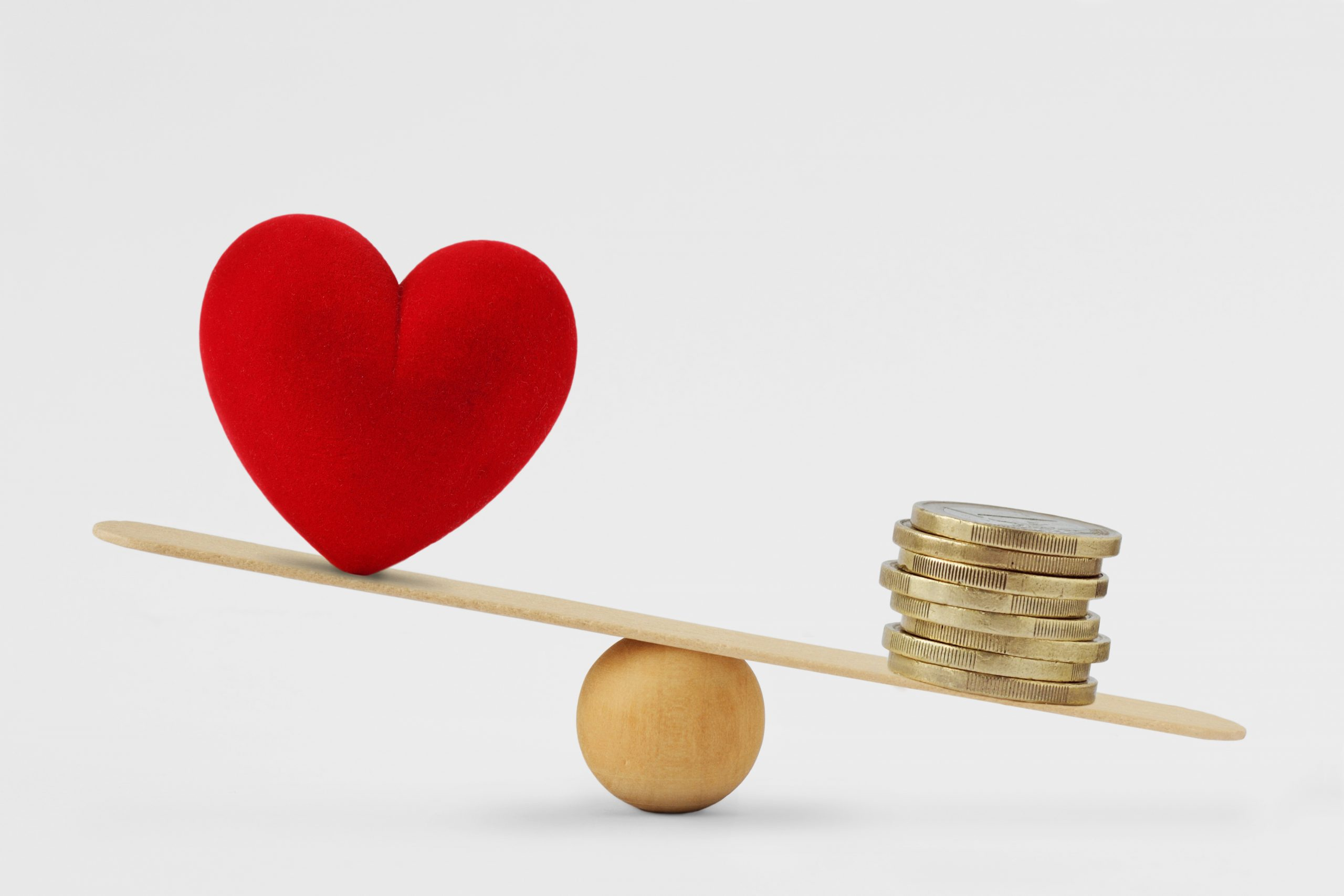 Heart and money on balance scale - Concept of money priority in life