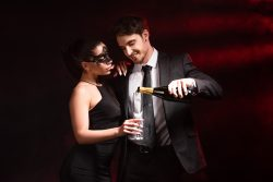 smiling man in formal wear pouring champagne to woman in dress and mask on black