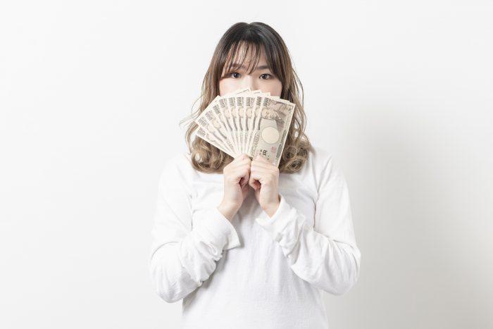 お金を手に持つ若い女性