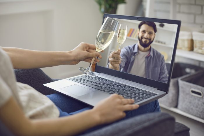 Online dating service. Young woman drinking champagne on webcam date with her handsome boyfriend at home