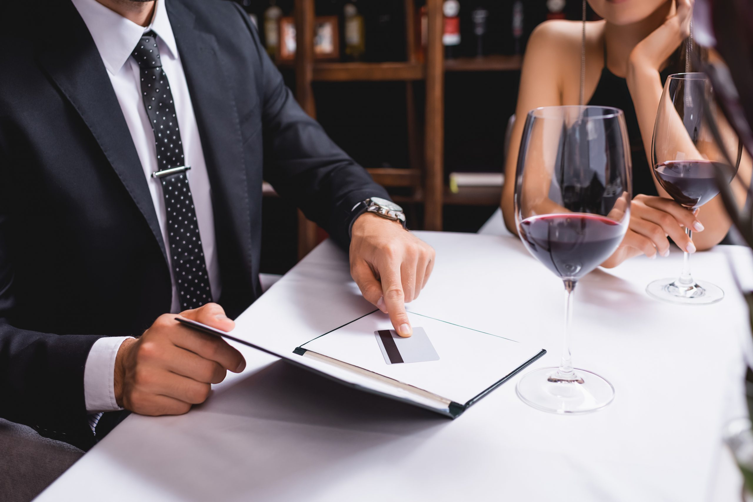 Cropped view of man putting credit card in restaurant bill near glasses of wine and girlfriend