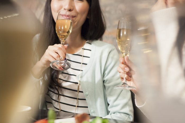 Young women are drinking champagne with friends